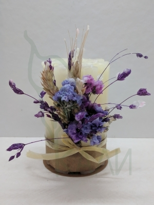 Handmade white candle with preserved flowers.